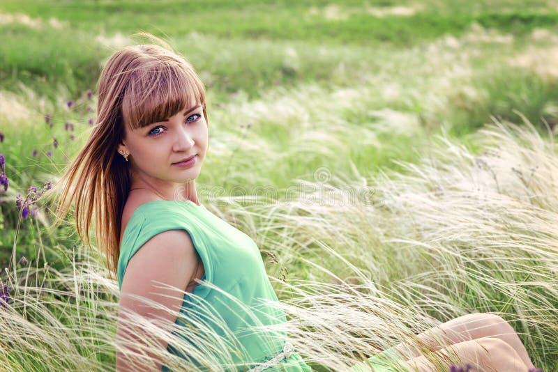 Het jonge sensuele meisje zit in openlucht in een gras royalty-vrije stock foto's