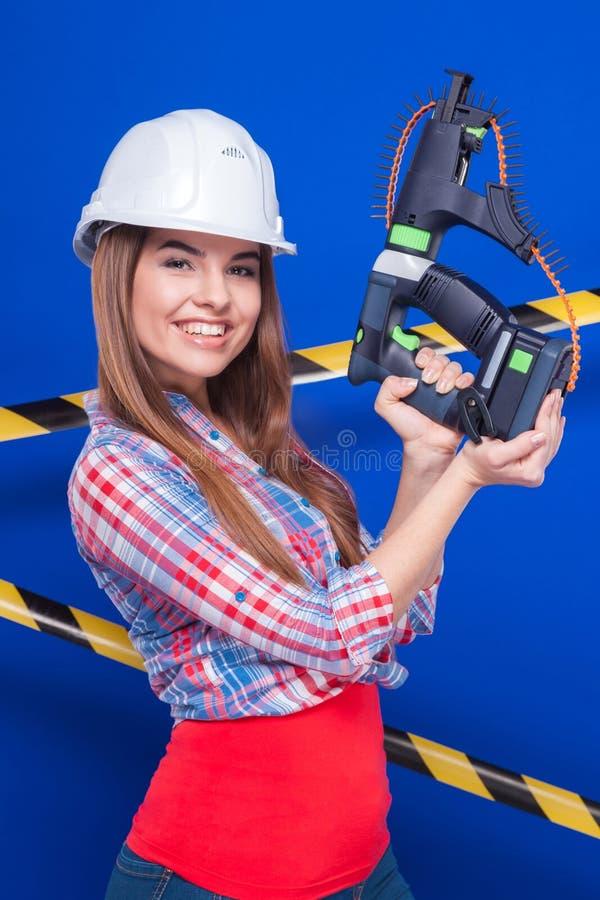 Het jonge sexy arbeidersmeisje chechered overhemd, binnen wit helm en Jean stock afbeelding