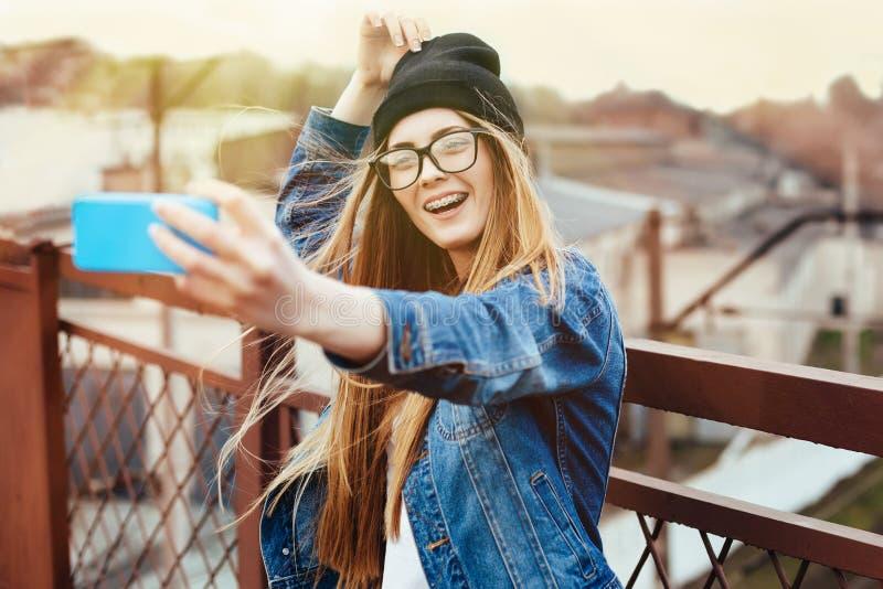 Het jonge sexy blonde hipster vrouw stellen voor selfie en het lachen Het dragen van jeansjasje, hipster zwarte hoed en glazen le stock afbeeldingen
