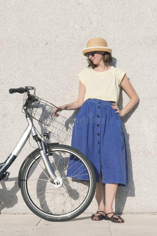 Het jonge sexy blondemeisje bevindt zich dichtbij de fiets stock afbeelding