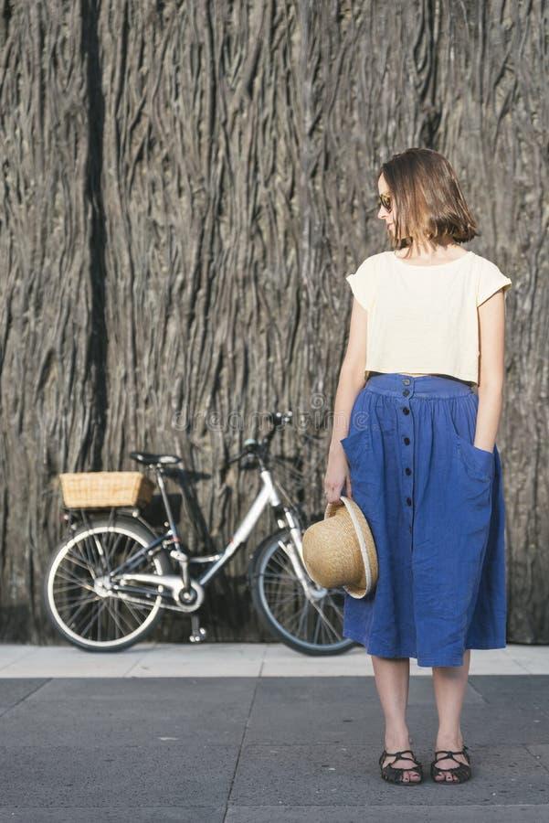Het jonge sexy blondemeisje bevindt zich dichtbij de fiets royalty-vrije stock foto's