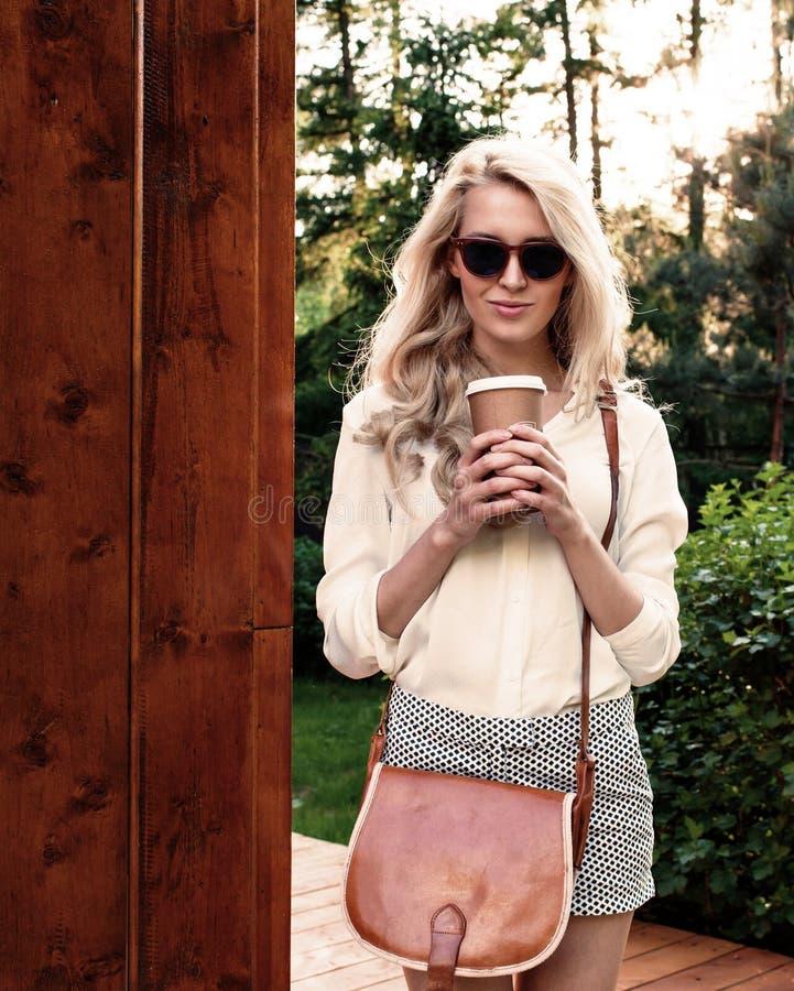 Het jonge sexy blondemeisje die met lang haar in zonnebril met bruine uitstekende zak een kop van koffie houden heeft pret en het royalty-vrije stock foto's