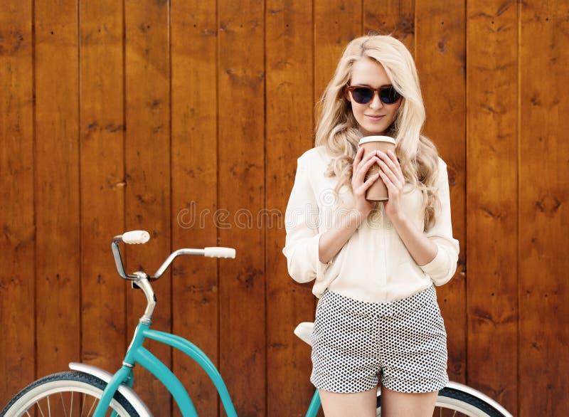Het jonge sexy blondemeisje met lang haar in zonnebril die zich dichtbij uitstekende groene fiets bevinden en een kop van koffie  stock afbeelding