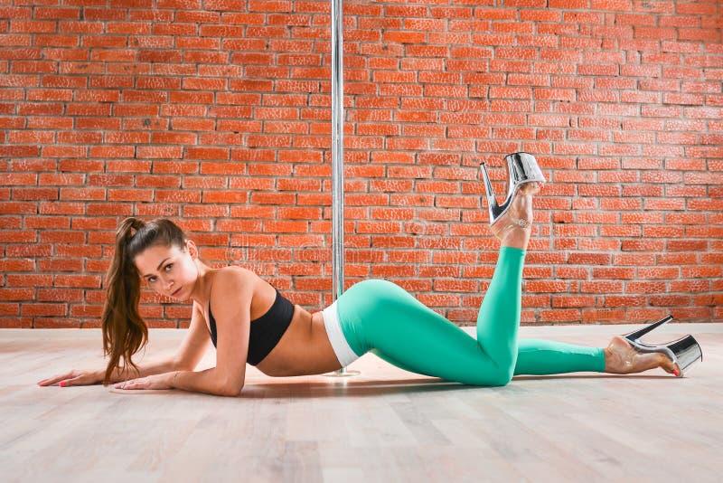 Het jonge sexy de vrouw van de pooldans stellen tegen bakstenen muur stock afbeelding
