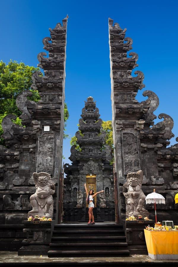 Het jonge sexy meisje van de silhouetschoonheid, vrouw op de achtergrondingang aan Balinese Hindoese tempel stock fotografie