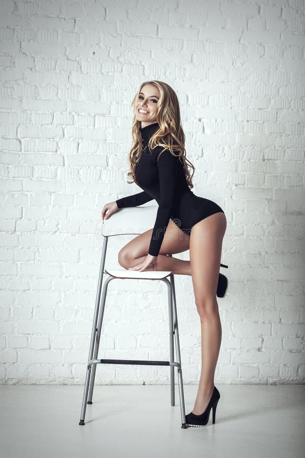 Het jonge sexy mooie blondevrouw stellen op stoel stock foto's