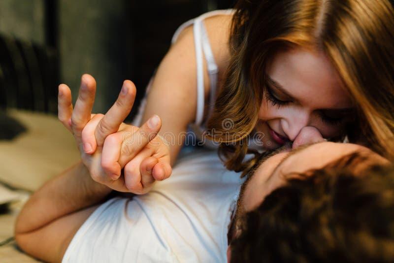 Het jonge sexy paar in liefde die in bed in hotel liggen, die op witte bladen omhelzen, sluit omhoog royalty-vrije stock foto's