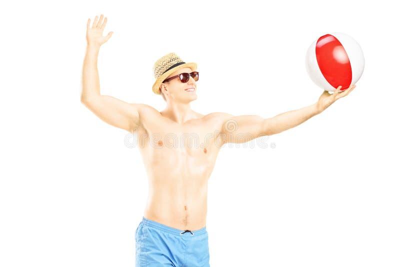Het jonge shirtless mens spelen met een strandbal stock foto's