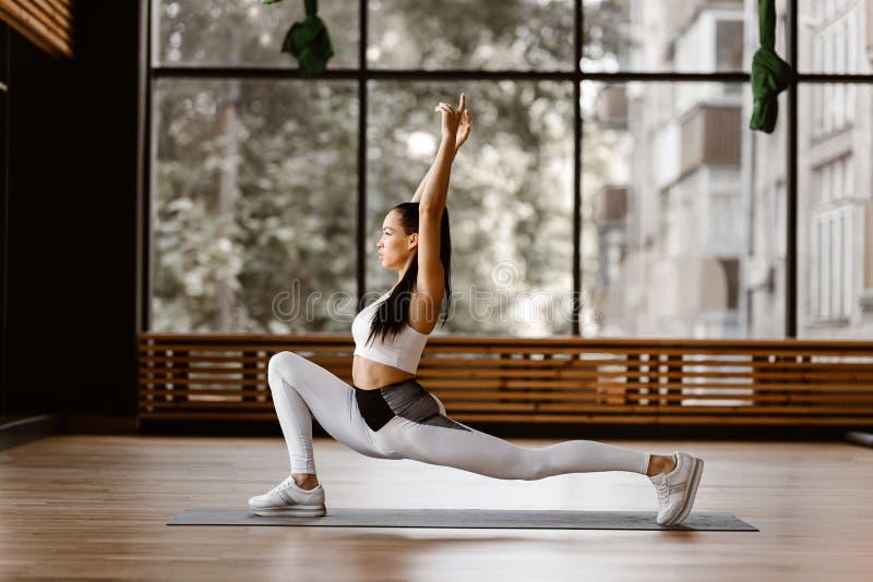 Het jonge slanke donker-haired meisje gekleed in witte sportenbovenkant en legging doet omgekeerde uitvalt en bereikt hoog wapens stock foto