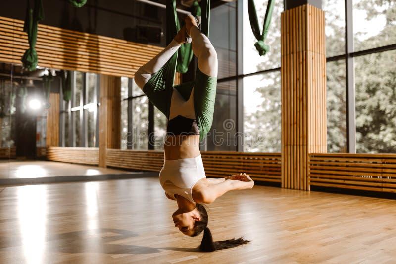 Het jonge slanke donker-haired meisje gekleed in witte sportenbovenkant en legging doet yoga op groene hangmat stock fotografie