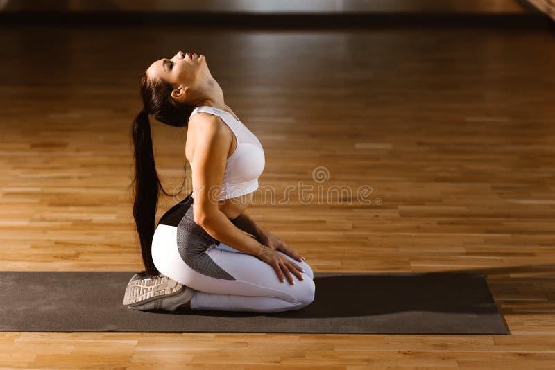 Het jonge slanke donker-haired meisje gekleed in witte sportenbovenkant en legging zit en warmt in de gymnastiek op stock foto