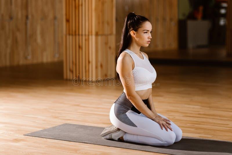 Het jonge slanke donker-haired meisje gekleed in witte sportenbovenkant en legging zit en warmt in de gymnastiek op royalty-vrije stock afbeeldingen