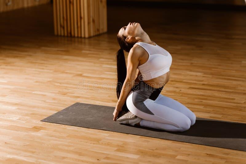 Het jonge slanke donker-haired meisje gekleed in witte sportenbovenkant en legging zit en warmt in de gymnastiek op stock afbeeldingen