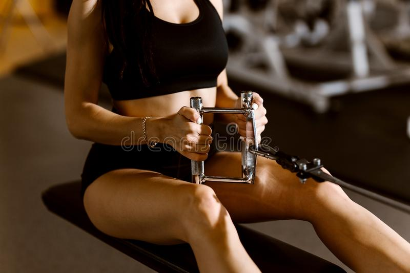 Het jonge slanke donker-haired meisje gekleed in zwarte sportenbovenkant en borrels werkt op de oefeningsmachine uit in de gymnas royalty-vrije stock fotografie