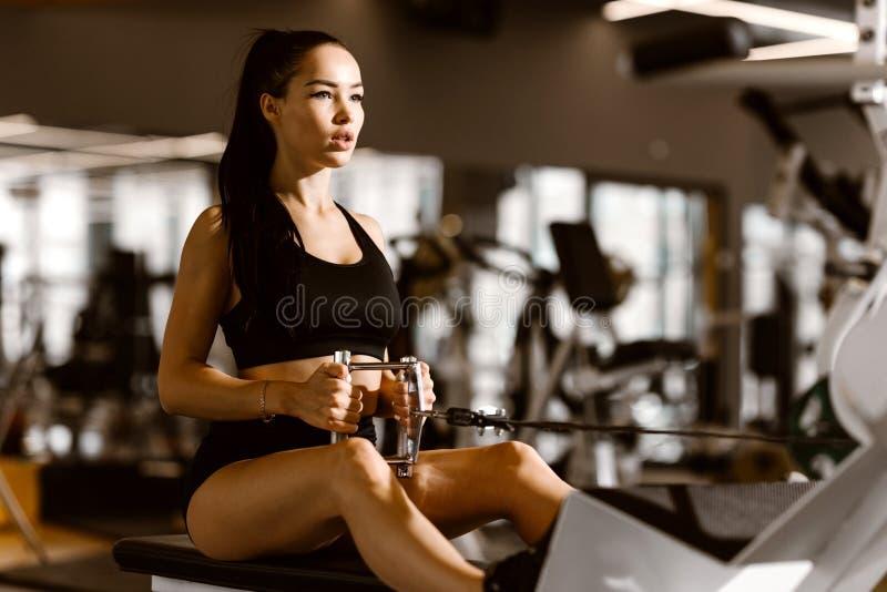 Het jonge slanke donker-haired meisje gekleed in zwarte sportenbovenkant en borrels werkt op de oefeningsmachine uit in de gymnas stock fotografie