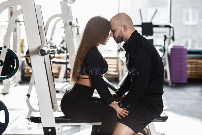 Het jonge slanke mooie meisje en de brutale atletische mens zitten samen op de sportbank zacht wat betreft hun royalty-vrije stock afbeeldingen