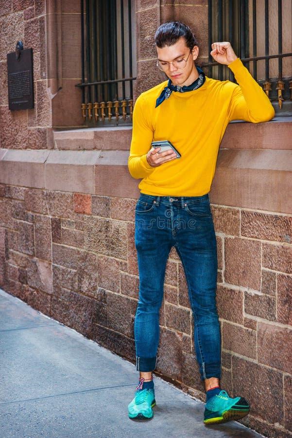 Het jonge Spaanse Amerikaanse Mens texting buiten in New York stock foto's