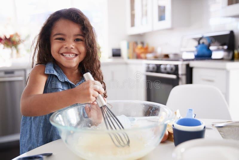 Het jonge Spaanse meisje die cake maken in de keuken op haar mengen, die sluit omhoog glimlachen royalty-vrije stock foto's