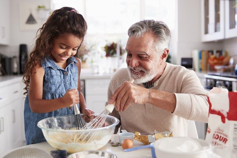 Het jonge Spaanse meisje en haar opa die cakemengsel zwaaien samen bij de keukenlijst, sluiten omhoog stock afbeeldingen
