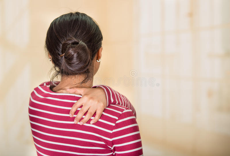 Het jonge Spaanse vrouw stellen voor camera die tekens die van schouderpijn tonen, handen op pijnlijk lichaamsdeel, verwonding ho royalty-vrije stock afbeelding
