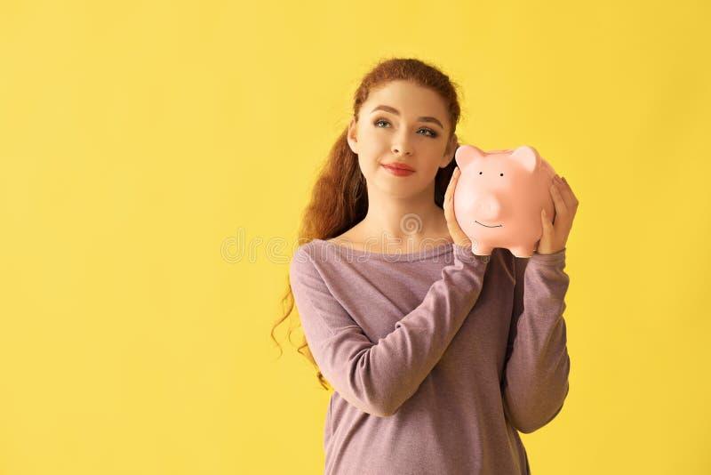 Het jonge spaarvarken van de vrouwenholding op kleurenachtergrond De besparingenconcept van het geld royalty-vrije stock afbeelding