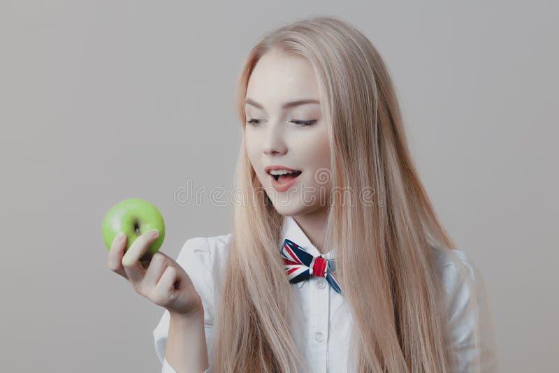 Het jonge speelse leuke blonde bijt groene appel stock fotografie