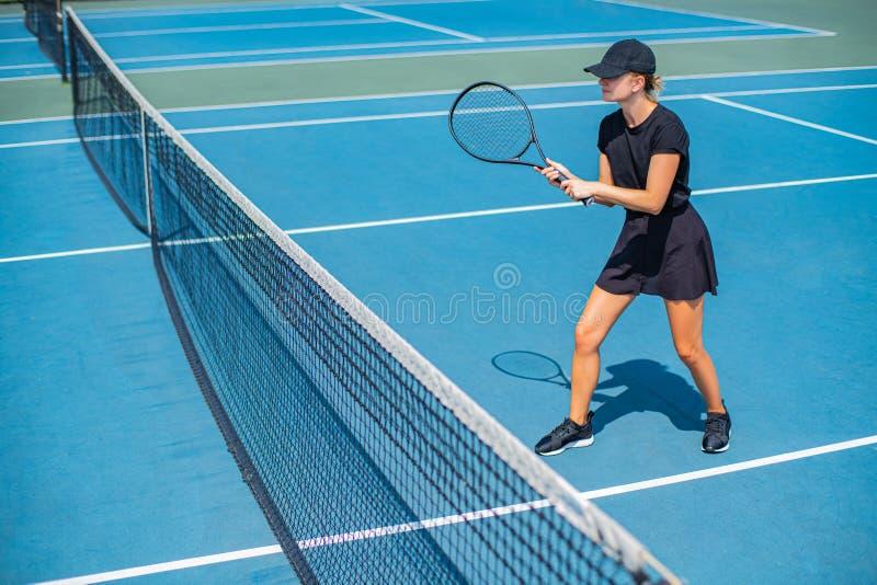 Het jonge speeltennis van de sportenvrouw op de blauwe tennisbaan stock foto's