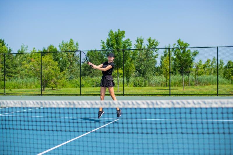 Het jonge speeltennis van de sportenvrouw op de blauwe tennisbaan stock afbeeldingen