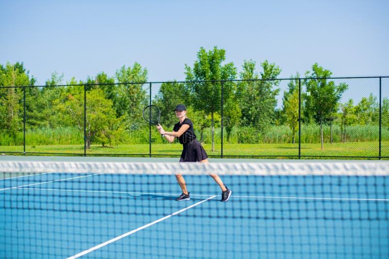 Het jonge speeltennis van de sportenvrouw op de blauwe tennisbaan royalty-vrije stock foto