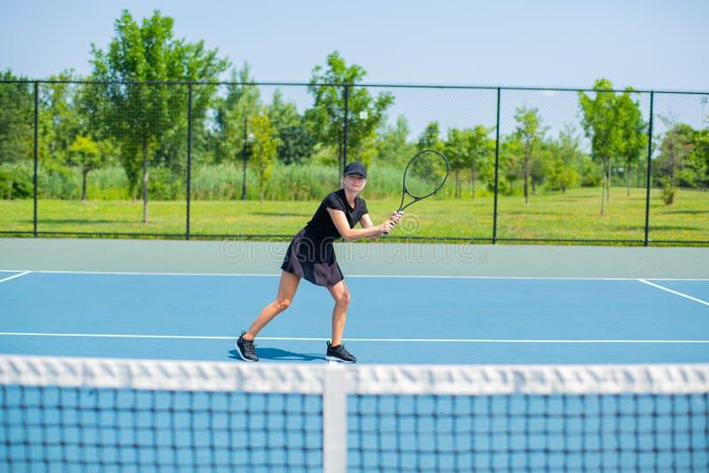 Het jonge speeltennis van de sportenvrouw op de blauwe tennisbaan stock afbeelding
