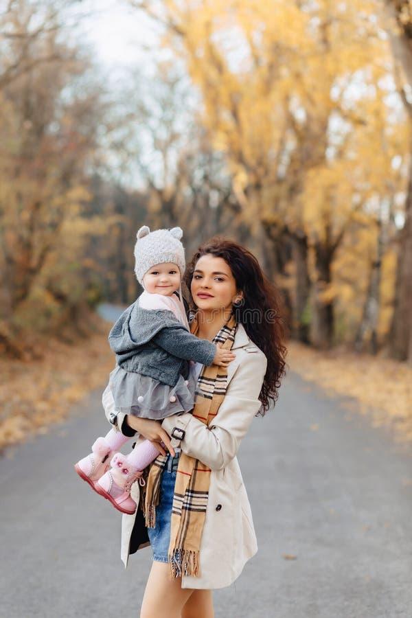 Het jonge spel van het vrouwenmamma met weinig dochter bij de weg van het de herfstpark royalty-vrije stock foto