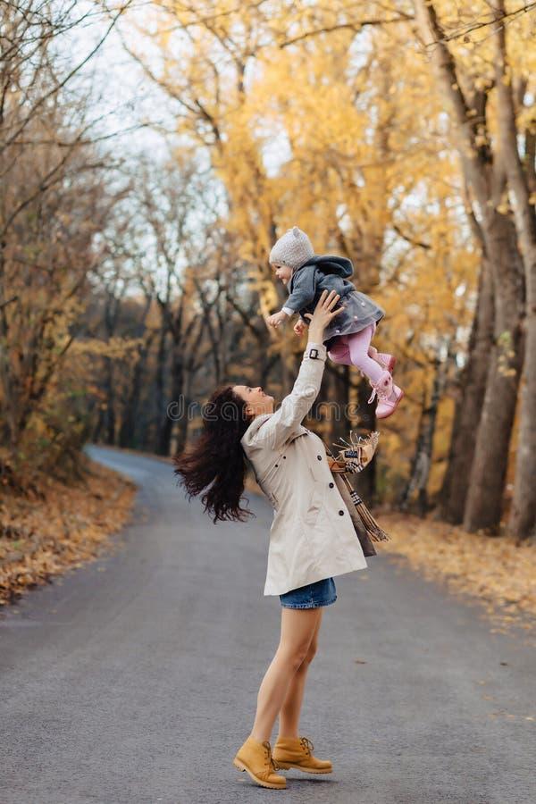 Het jonge spel van het vrouwenmamma met weinig dochter bij de weg van het de herfstpark stock foto