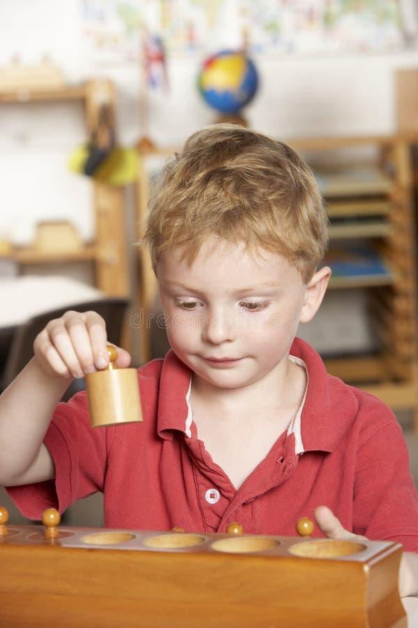 Het jonge Spelen van de Jongen in Montessori/Pre-School stock foto