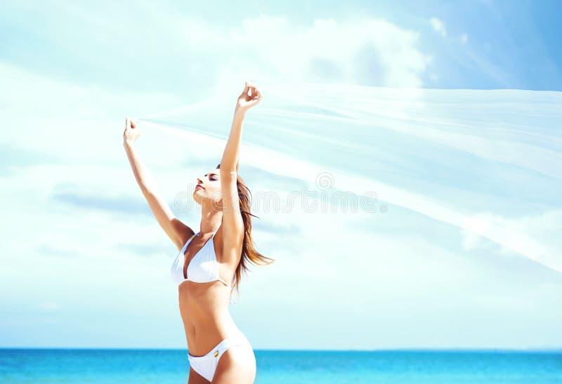 Het jonge, sportieve en gelukkige vrouw stellen met een blazende zijde op su royalty-vrije stock afbeelding