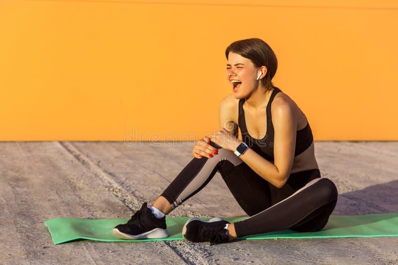 Het jonge sportieve meisje in zwarte sportwear zitting op mat en heeft een sterk gekwetst probleem met knie, pijnlijke kramp Grij stock afbeelding