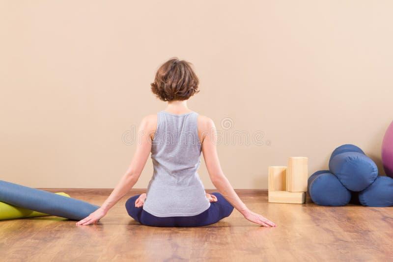 Het jonge sportieve vrouw uitrekken zich bij gymnastiek stock foto's
