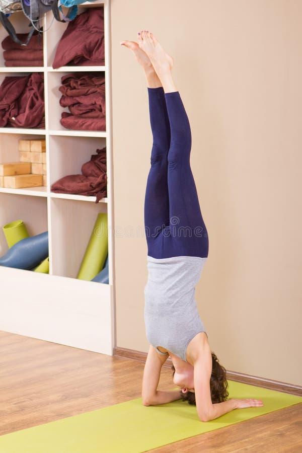 Het jonge sportieve vrouw uitrekken zich bij gymnastiek royalty-vrije stock afbeeldingen