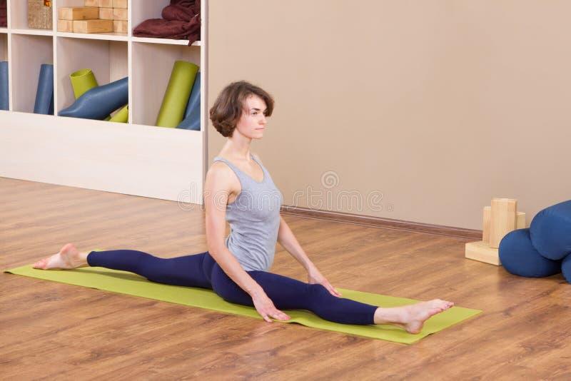 Het jonge sportieve vrouw uitrekken zich bij gymnastiek stock afbeelding