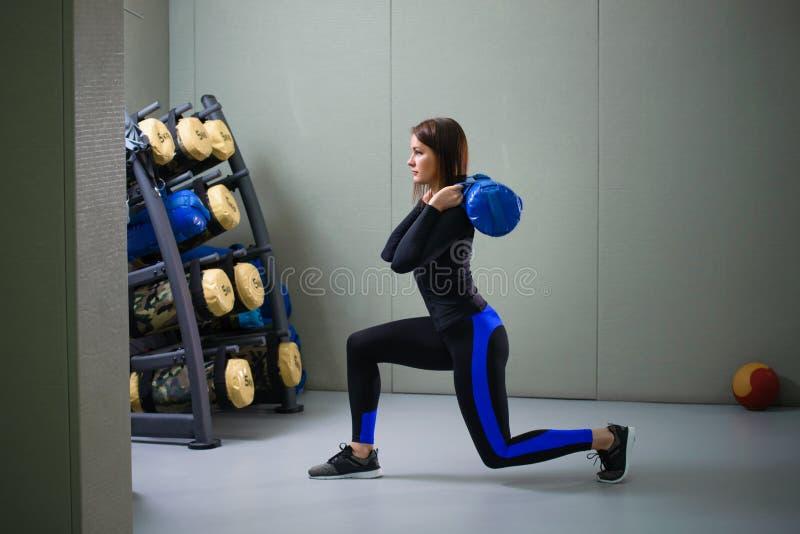 Het jonge sportieve vrouw uitwerken met geschiktheidszak bij gymnastiek, valt oefening uit stock foto