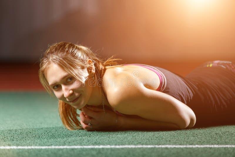 Het jonge sportvrouw ontspannen op vloer na opleiding royalty-vrije stock foto's