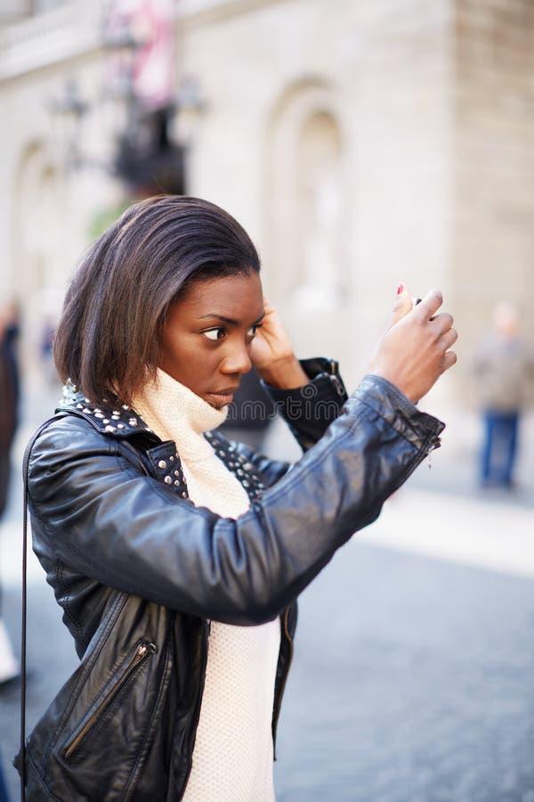 Het jonge student lopen door de stad hield even op om het haar te bevestigen stock afbeelding