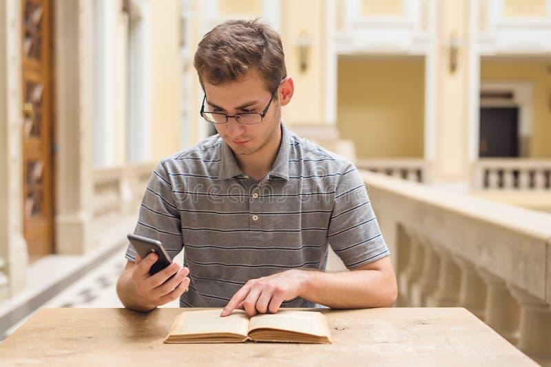 Het jonge studentenkerel leren en gebruikt zijn telefoon royalty-vrije stock afbeelding