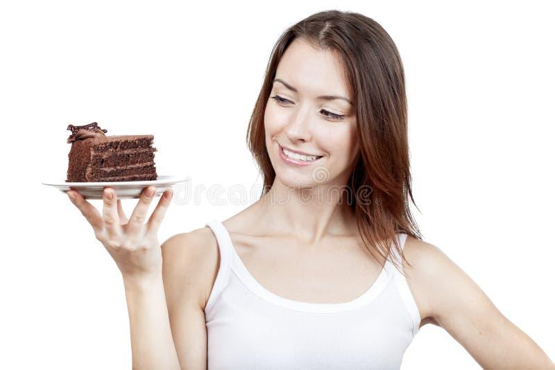 Het jonge stuk van de vrouwenholding van chocoladecake stock afbeelding