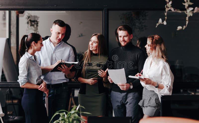 Het jonge team van collega's werkt met documenten en bespreekt het project in een modieus modern bureau Het werkproces in stock foto's