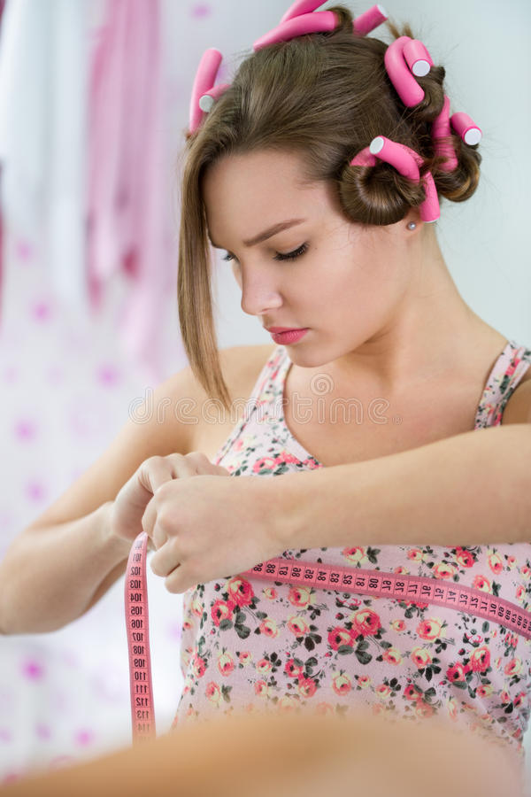 Het jonge tienermeisje concentreerde zich bij het meten van borst stock afbeeldingen