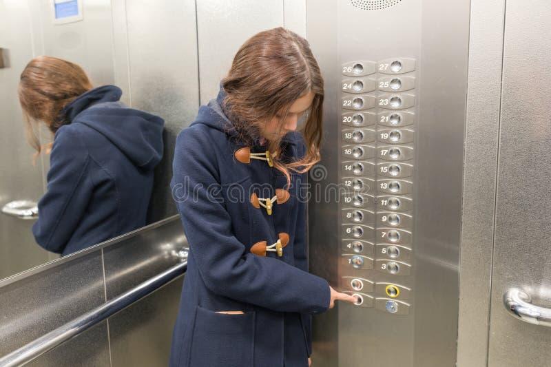 Het jonge tienermeisje in lift, drukt de liftknoop stock afbeelding