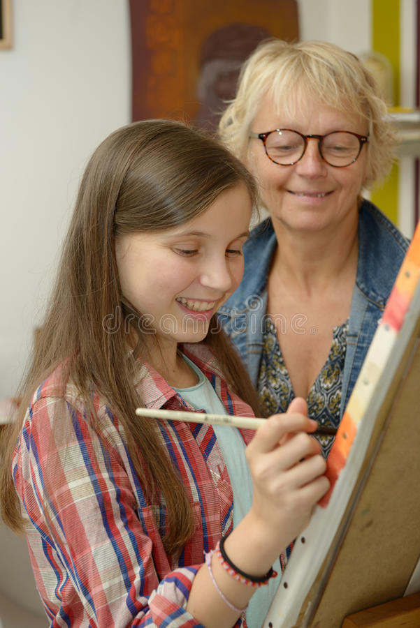 Het jonge tienermeisje schilderen met haar leraar royalty-vrije stock afbeelding