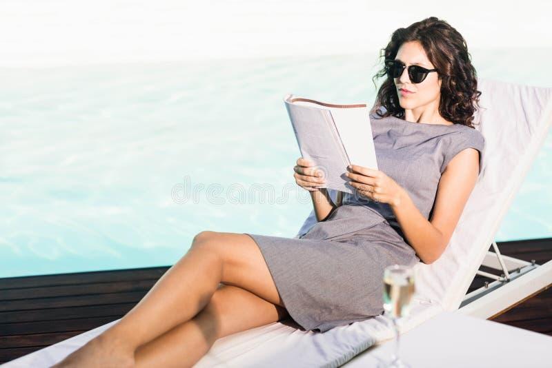Het jonge tijdschrift van de vrouwenlezing dichtbij poolside stock foto's