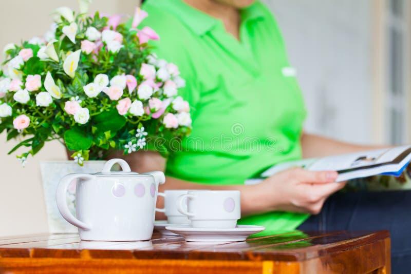 Het jonge tijdschrift van de vrouwenlezing wit die porselein voor thee wordt geplaatst of cof royalty-vrije stock foto's