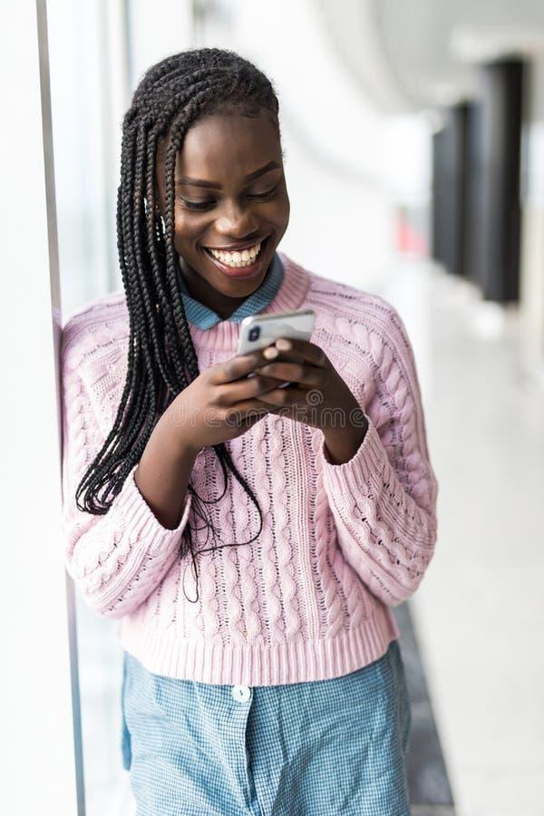 Het jonge toevallige Afrikaanse vrouw typen op mobiele telefoon voor panoramische vensters stock foto